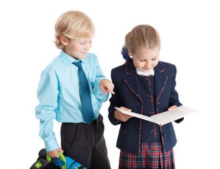 colegiala: Colegial con la cartera se�ala en libro en schoolgirl`s manos mientras ella la lectura, aislado sobre fondo blanco