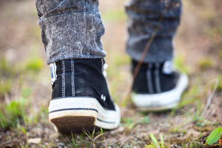 unrecognizable person: Unrecognizable person in rubber shoes walking on footpath, rear view Stock Photo