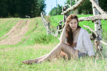 young woman nude: Young woman with an unbuttoned shirt and nude breast enjoying the sun on a countryside Stock Photo