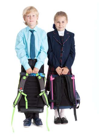 colegiala: Colegial y colegiala con mochilas en manos de pie juntos, aislados en fondo blanco