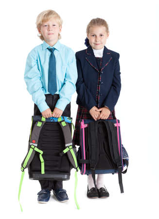 schoolgirl uniform: Schoolboy and schoolgirl with schoolbags in hands standing together, isolated on white background Stock Photo