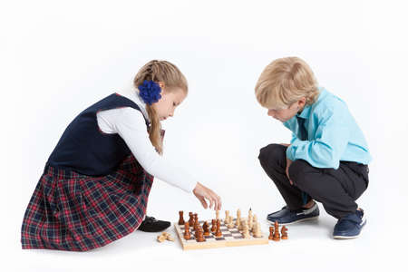 uniformes: Muchacho de pelo rubio y una niña a los alumnos en el ajedrez de juego uniforme de la escuela, aislado más de fondo blanco Foto de archivo