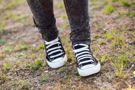 unrecognizable person: Unrecognizable person in rubber shoes walking on footpath