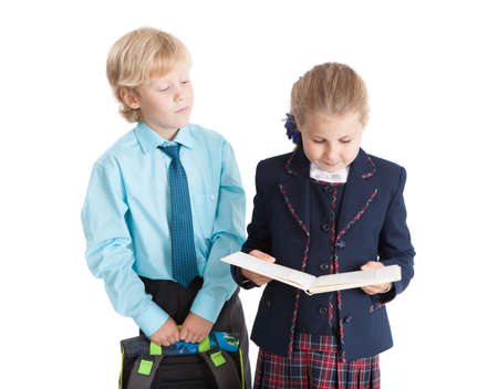 schoolgirl uniform: Schoolboy with schoolbag in hands standing near the schoolgirl while she reading book, isolated on white background