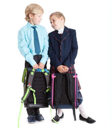 uniforme escolar: Alumno de primer grado en uniforme escolar con mochilas que buscan el uno al otro, de cuerpo entero, aislado en fondo blanco