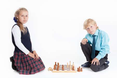 uniformes: Niño y niña en uniforme escolar jugando al ajedrez, mirando a cámara, aislado en fondo blanco