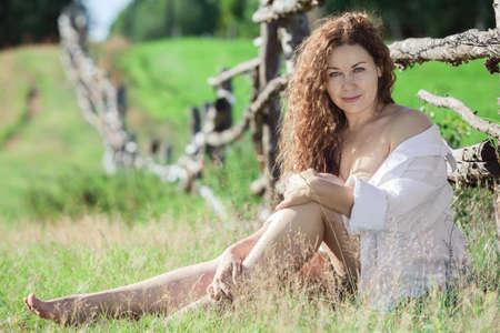 Curly sexy brunette cheveux en chemise blanche assis près de la clôture en bois dans les prairies Banque d'images - 44554582