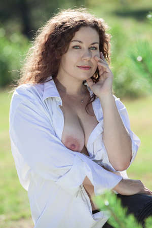 nude nature: Curly hair brunette woman with nude breast under white shirt, summer season, nature