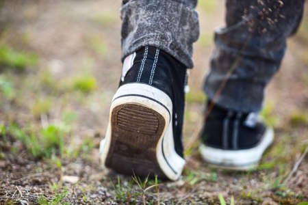 unrecognizable person: Unrecognizable person in running shoes walking on footpath, rear view