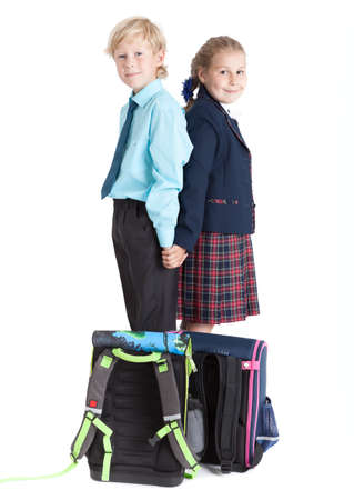 floor standing: Schoolboy and schoolgirl with schoolbags on floor standing back to back, isolated on white background