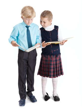 colegiala: Colegial y colegiala de lectura de libros elementales entre sí, de cuerpo entero, aislado en fondo blanco