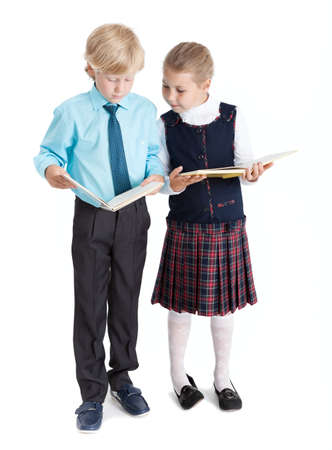 schoolgirl uniform: Elementary schoolboy and schoolgirl reading books each other, full length, isolated on white background