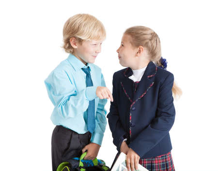schoolkids: Pretty schoolkids talking each other, pupils in uniform, isolated on white background Stock Photo