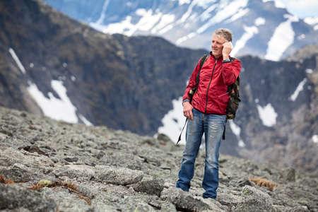 hablando por telefono: Viajero con una mochila hablando por teléfono celular en el fondo de las montañas