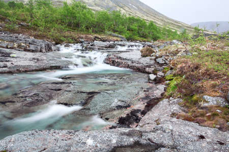 alpine tundra: Blue clear water of river flowing from the peaks of mountains, long exposure
