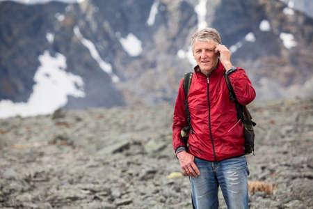 Portrait of mature Caucasian hiker talking on a cellular phone in mountains Foto de archivo