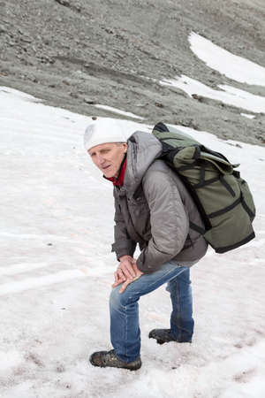 extreme sports: Mature Caucasian hiker standing on the slippery steep slope of mountain and looking at camera Stock Photo