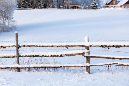 fence: Snowy fence of rural paddock in village, winter season
