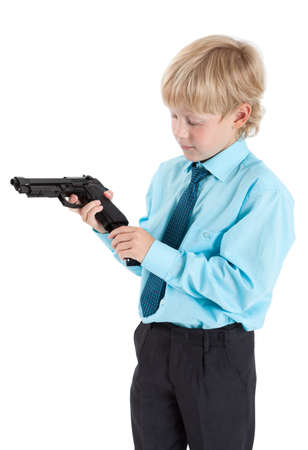 child portrait: Caucasian boy in shirt with tie charging black gun in hands, isolated on white background