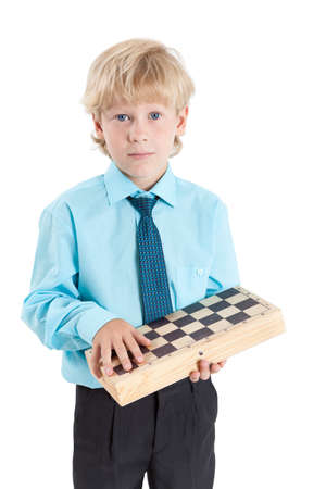 school age boy: School age boy holding chessboard and looking at camera, isolated on white background Stock Photo
