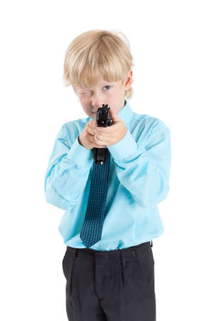 aiming: Caucasian blond boy aiming with black gun in hands, isolated on white background