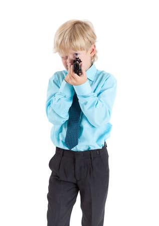 pistola: Retrato de raza caucásica niño rubio apunta con el arma negro en las manos, aisladas sobre fondo blanco Foto de archivo