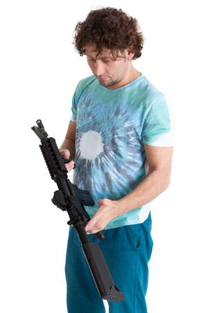 machinegun: Adult man bungle holding machinegun in hands and looking at weapon, isolated on white background