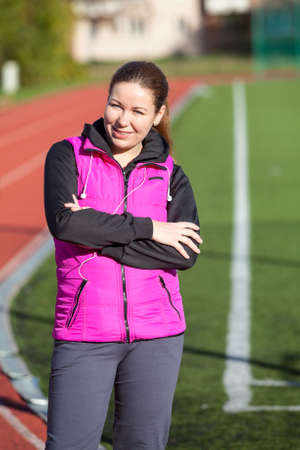 clasped hands: Happy Caucasian young woman portrait with clasped hands, standing at the stadium in sport clothes