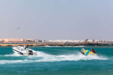 egypt: HURGHADA, EGYPT - CIRCA NOV, 2015: People ride on the inflatable banana in the Red Sea bay with motor boat. Entertainment is on the Hurghada resort