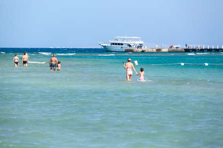 hurghada: HURGHADA, EGYPT - CIRCA NOV, 2015: Adults and children walk on the shallow of the Red Sea. Summer resorts are in the Hurghada, Egypt