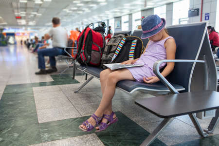 gatehouse: Tired Caucasian girl sleeping in the waiting room at the airport terminal, sitting on a chair.