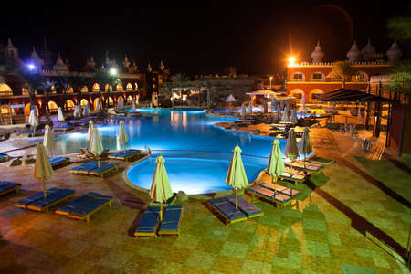 alf: HURGHADA, EGYPT - CIRCA NOV, 2015: Night illumination of swimming pool and poolside is in the area of Egyptian hotel. The Alf Leila Wa Leila spa 1001 Nights is one of the Pickalbatros Editorial