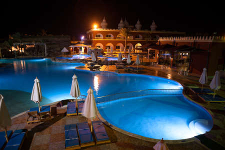 alf: HURGHADA, EGYPT - CIRCA NOV, 2015: Night illumination of empty swimming pool and poolside is in the area of Egyptian hotel. The Alf Leila Wa Leila spa 1001 Nights is one of the Pickalbatros