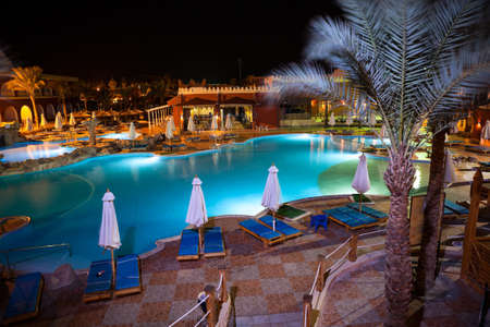 alf: HURGHADA, EGYPT - CIRCA NOV, 2015: View at the night illumination of swimming pool and poolside of the Egyptian hotel. The Alf Leila Wa Leila spa 1001 Nights is one of the Pickalbatros