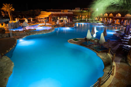 alf: HURGHADA, EGYPT - CIRCA NOV, 2015: View at the night illuminated swimming pool and poolside of the Egyptian hotel. The Alf Leila Wa Leila spa 1001 Nights is one of the Pickalbatros Editorial