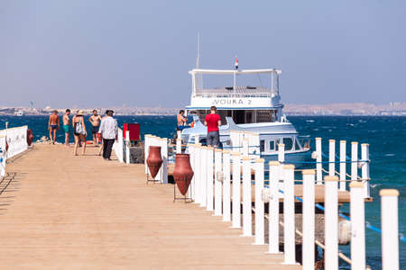 hurghada: HURGHADA, EGYPT - CIRCA NOV, 2015: Pier for ships mooring is on the Red Sea coast line. People walk on the wooden planks for swimming and voyaging