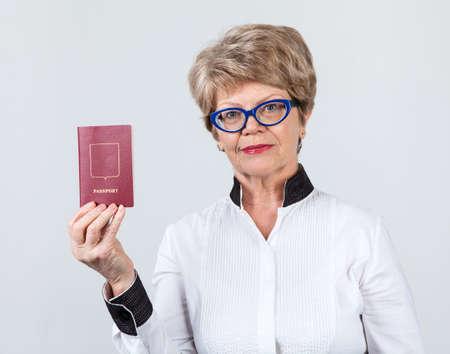 Portrait of Caucasian mature woman holding red passport, gray background Stock Photo