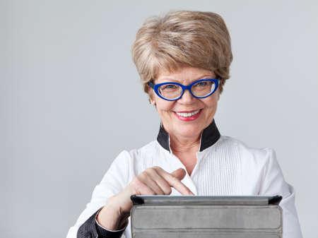 communicatie: Vrouw een gepensioneerde klikken op het touchscreen van de tablet met een glimlach, grijze achtergrond Stockfoto