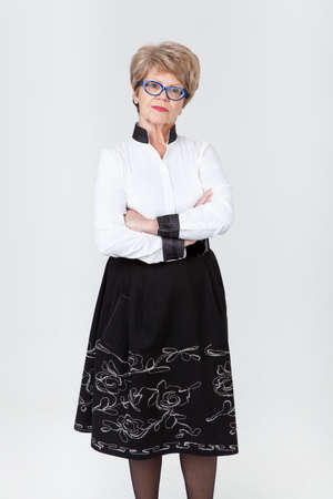 strict: Strict senior Caucasian woman with folded arms, gray background