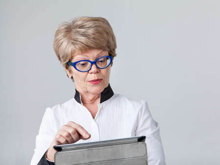viewing: Senior surprised woman trying to push the button at the tablet screen, portrait on a gray background Stock Photo