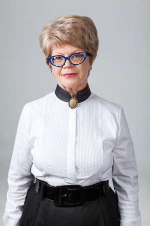 wrinkled: Portrait of attractive senior woman in eyeglasses, gray background Stock Photo