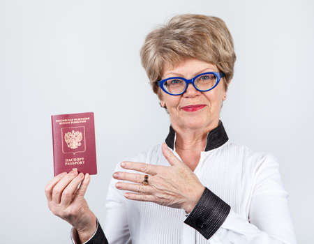 beautiful mature woman: Happy Caucasian senior woman pointing at red passport, gray background
