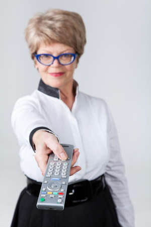 foreground focus: Elderly woman stretching tv remote control in hand, foreground focus, grey background