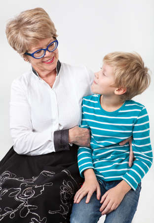 kinship: Caucasian elderly woman and young boy together looking each other, portrait on a gray background