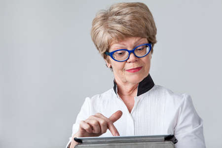 smirk: Senior woman with a smirk pushing the button at the tablet screen, portrait on a gray background