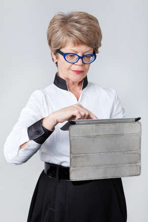 senior woman: Concentrated senior woman pushing the button at the tablet screen, portrait on a gray background