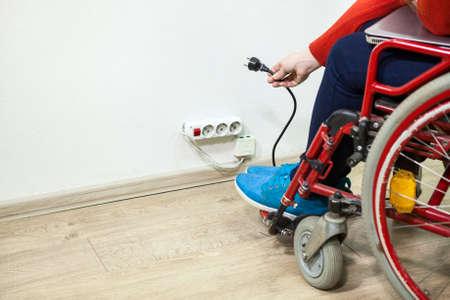 paraplegic: Caucásico persona con discapacidad tiene algunos problemas, mientras que la inserción de enchufe en una toma, copyspace Foto de archivo