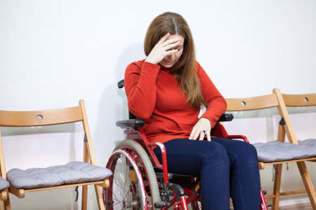 inconvenience: Paralyzed legs sad woman in invalid chair covers her face with hand while sitting between chairs Stock Photo
