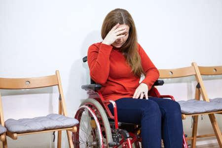hemorragia: Piernas paralizadas triste mujer en silla de inválido cubre la cara con la mano mientras está sentado entre las sillas