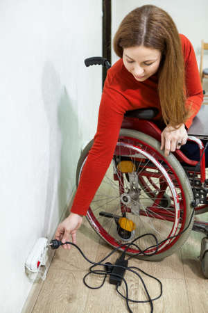 plug in: Young disabled woman sitting wheelchair with power plug in hand, stretching to power outlet in wall
